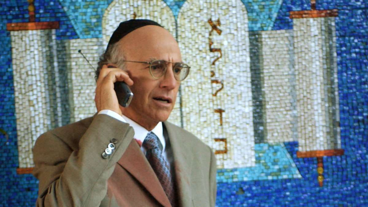 Larry David on cell phone in yarmulke Jewish mosaic behind