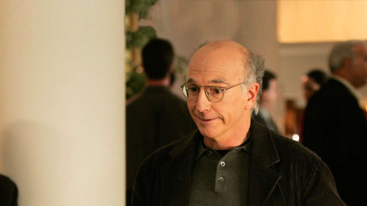 Larry David smiling right had out left hand in pocket