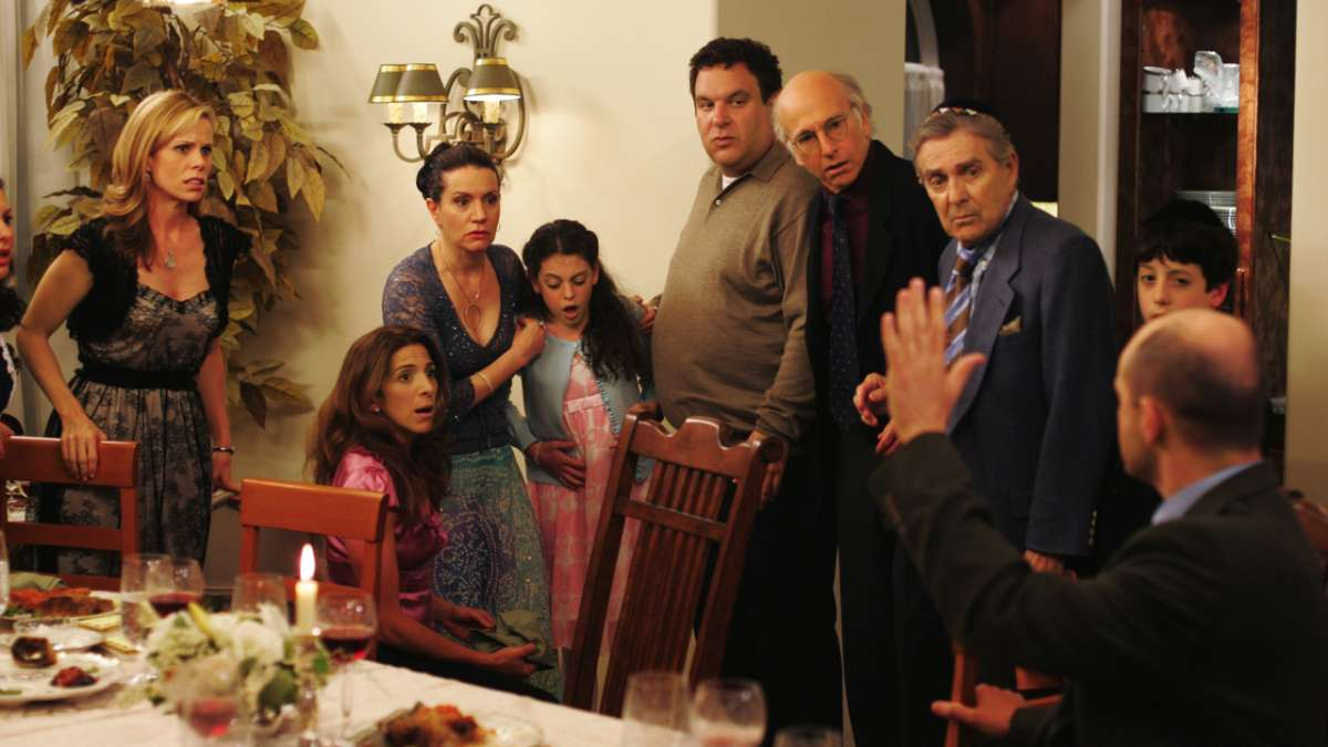 """Cheryl, Susie, Jeff Greene, Larry David and other Seder guests look at man with hand up"""