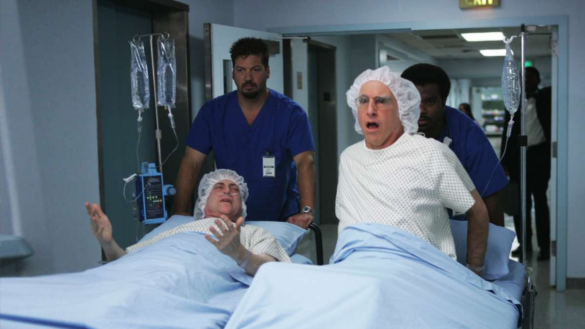 Richard Lewis and Larry David sitting up on gurneys in hospital