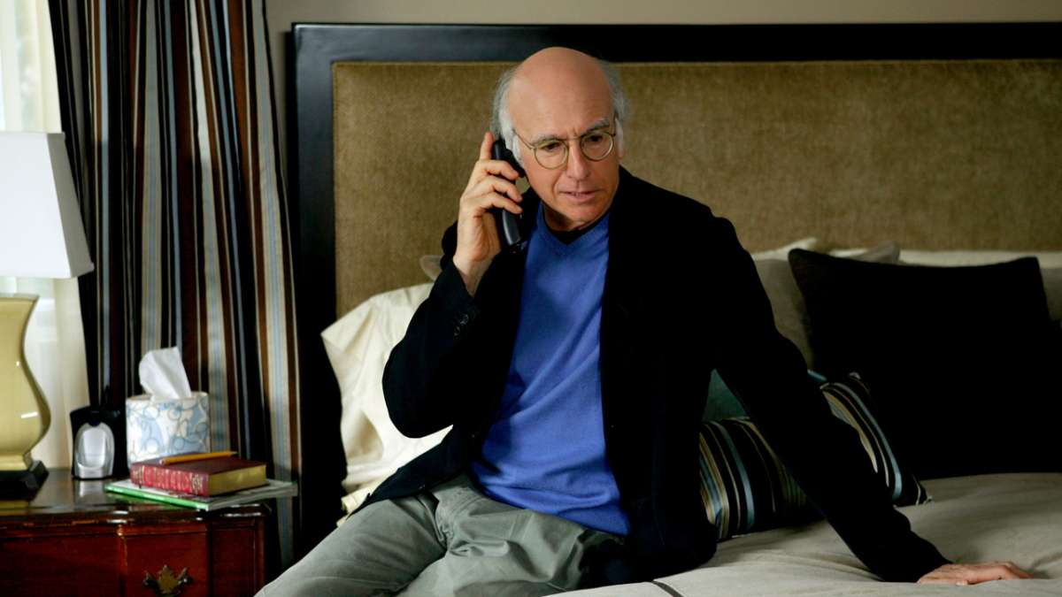 Larry David on phone sitting on bed