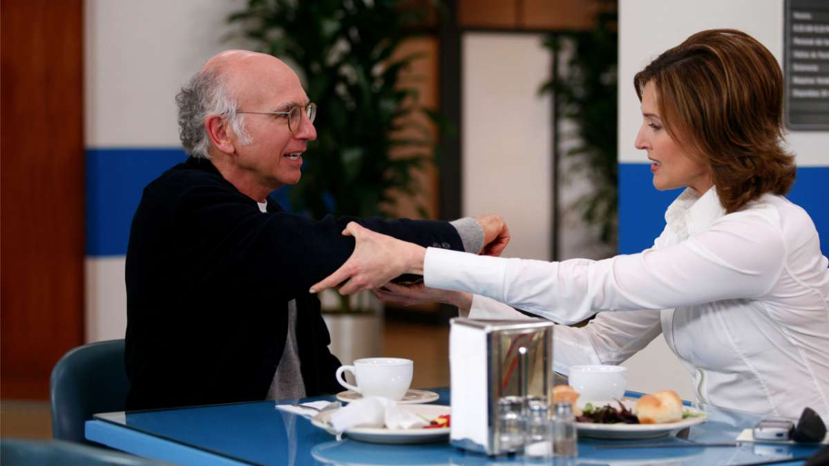 Woman holding Larry David's arm in hospital cafeteria