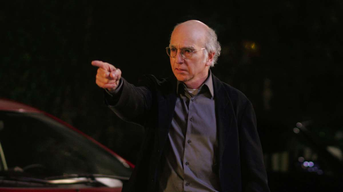 Larry David pointing outdoors at night