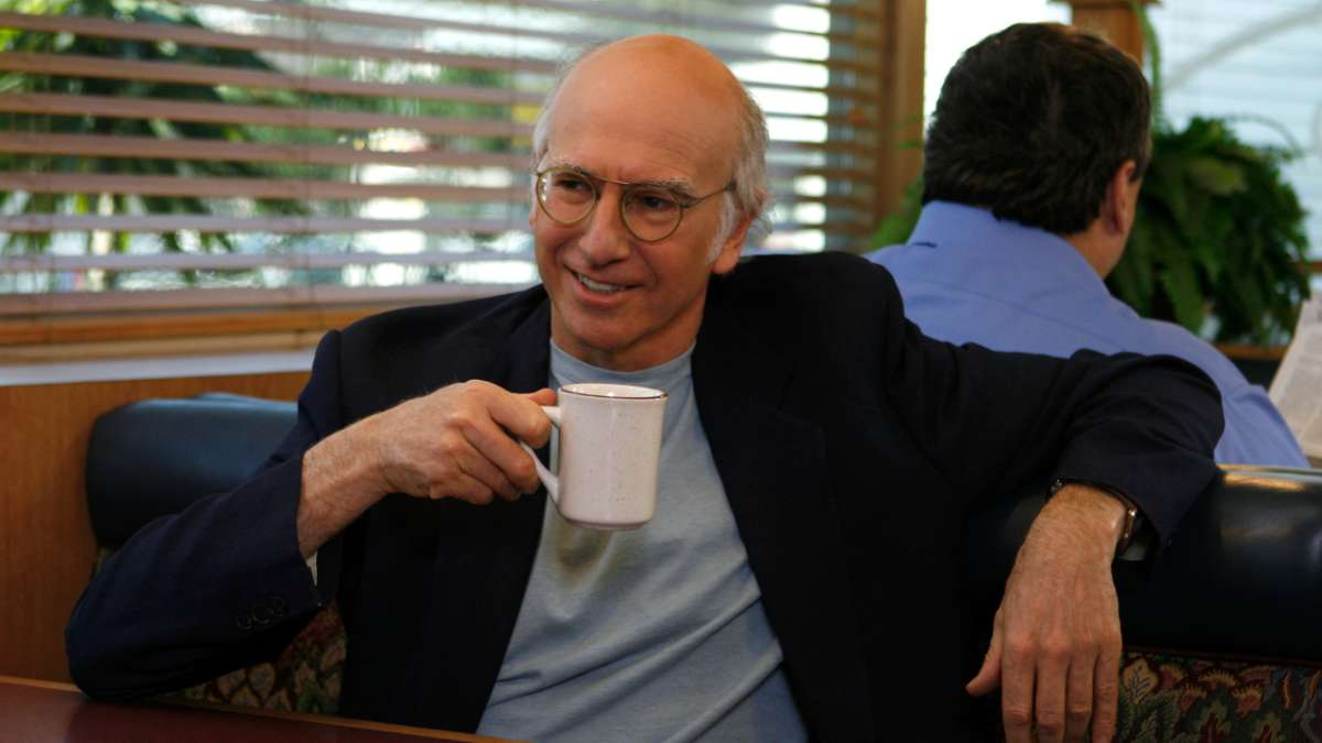 Larry David in diner booth drinking coffee